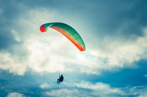 Paragliding Extreme Sport With Blue Sky And Clouds On Background