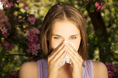 Young woman with allergy during sunny day is wiping her nose.M